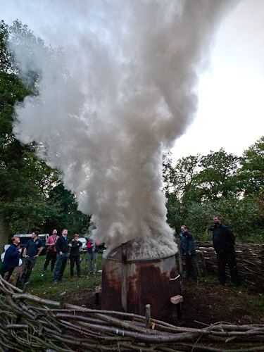 The charcoal kiln has heated up and the smoke starts to rise. It is quite dark in colour, indicating that it is still full of moisture.