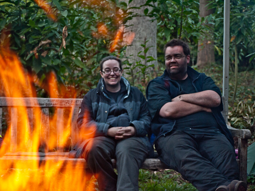 As with all good charcoal burns, a nearby fire is lit to provide heat and for cooking. Two volunteers on the charcoal-making course enjoy a break.