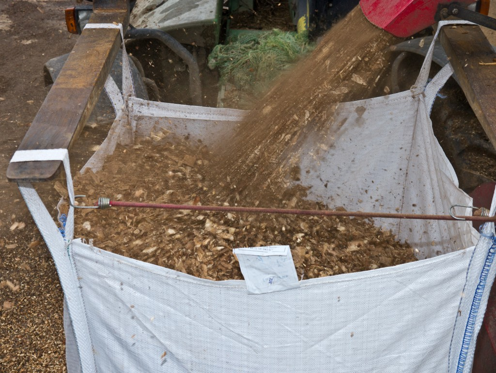 The first giant bag is nearly full of OneOak woodchip