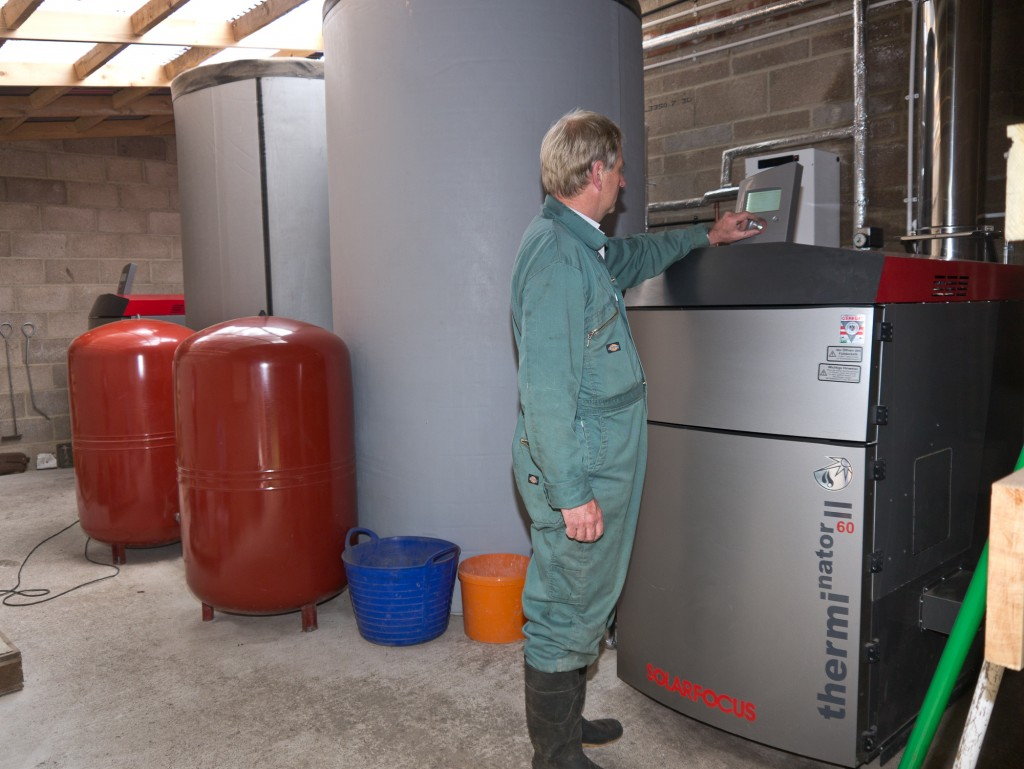 James Norman of Oxfordshire Renewables adjusts one of the boilers at Braziers Park