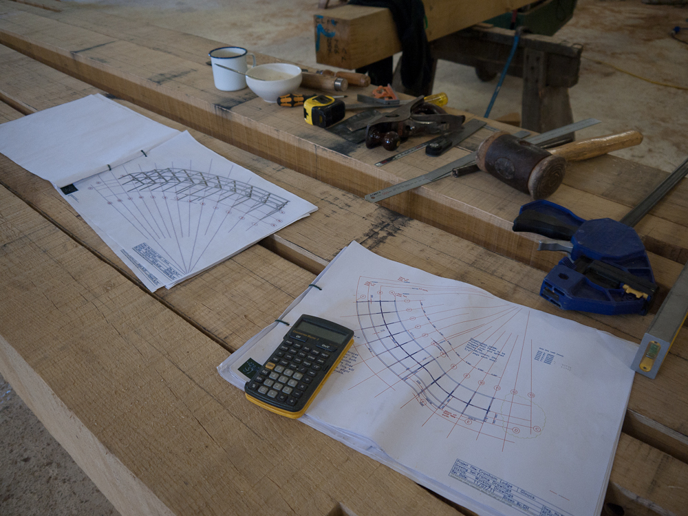 Set among the beams and working tools, the working drawing for the new build shows the curved grid design of the new build