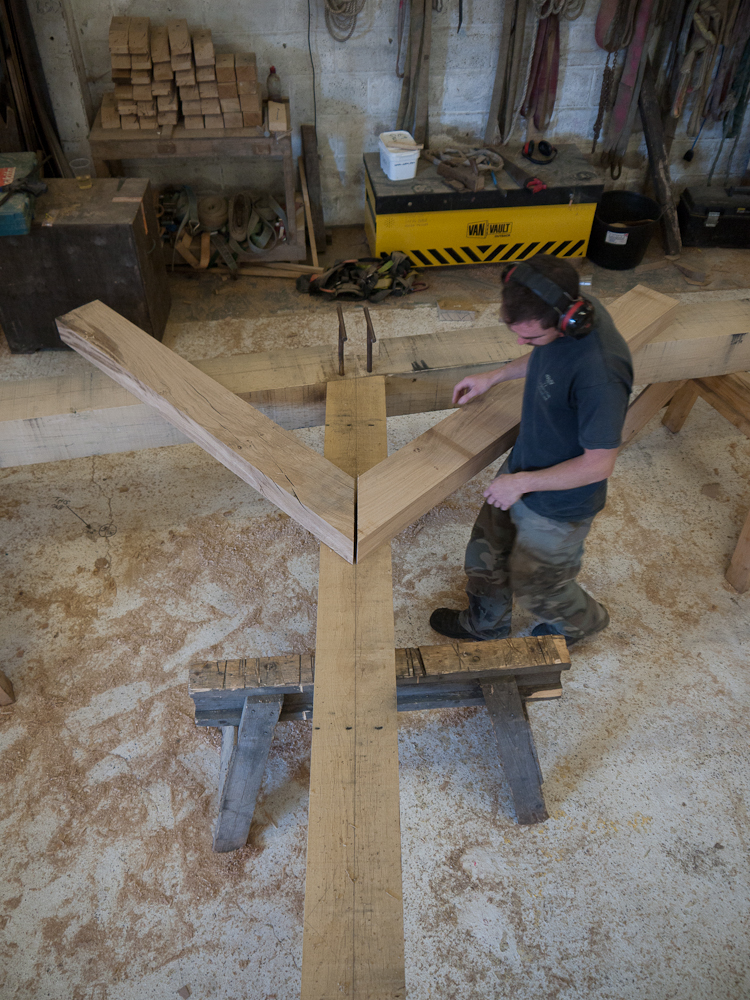 Carpenter Matt Collins marks out the two timber braces against the main frame after they have been sawn and planed.