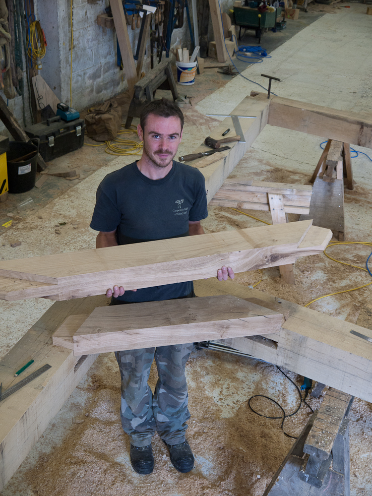 The two braces complete and ready to test for fitting into the newly created mortices in the main frame.  Carpenter Matt Collins has been timber framing for five years.