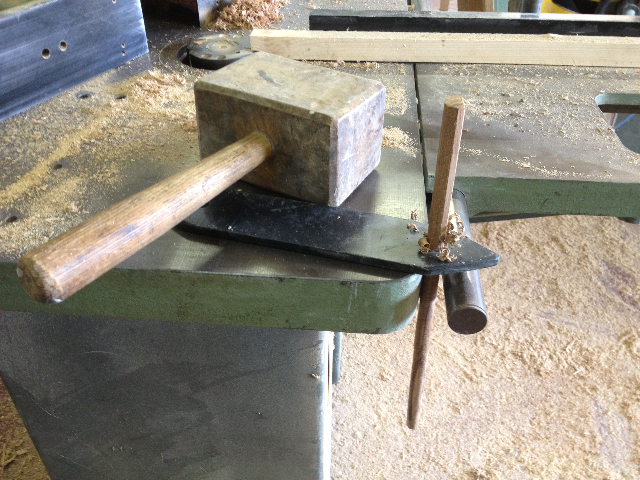 making pegs by driving square oak through a metal piece with round holes!